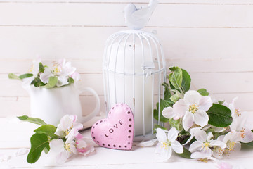 Spring apple blossom, candle in decorative bird cage  and little