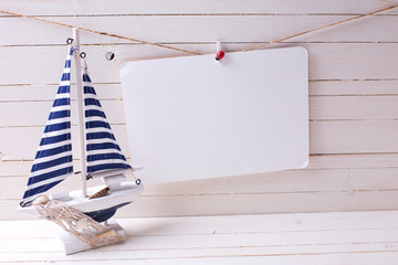 Decorative sailing boat and   empty tag on clothes line on woode