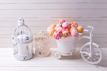 Cake pops  in decorative bicycle and candles  on white wooden ba