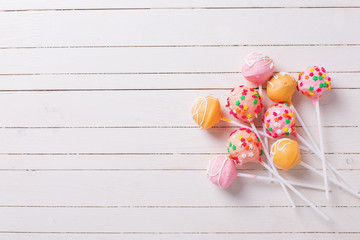 Cake pops on white  painted wooden background.
