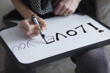 Woman writing I love you message on white board. Love message writing,selective focus