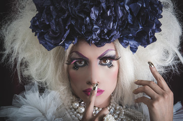 Drag queen with spectacular makeup, glamorous trashy look, posing while using hands and fingers