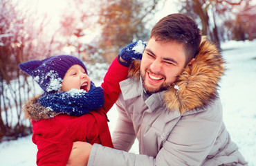 active father and son playing snowballs in winter park