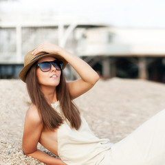 Happy fashion dressed woman in hat rest sitting on a beach.