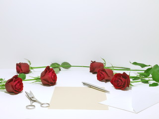 letter and roses on the white table