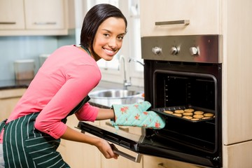 Smiling woman baking biscuits
