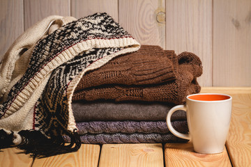 Pile of knitted sweaters and a cup on a wooden background