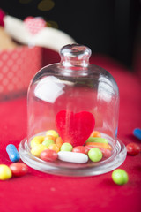 Close-up of pile of colorful sweets under glass dome. Bokeh