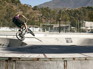 Young boy doing jumps on his BMX bike in a skate park.