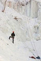 unidentifiable Ice climber climbing a frozen waterfall, in Ontario Canada