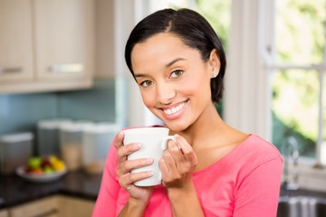 Smiling brunette holding white cup