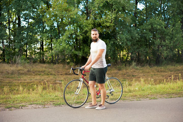 Young hipster style man posing with bicycle
