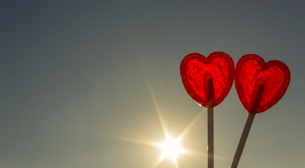 Two red lollipops shaped as heart agains sun