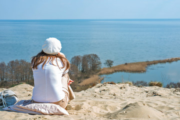 Woman in a beret sits on a mountain and looking at the sea