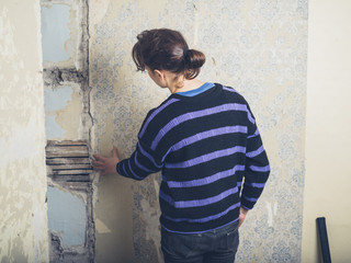Woman examing lath wall