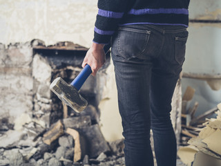 Woman opening up fireplace with sledge hammer
