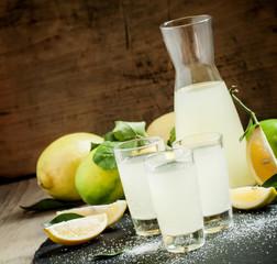 Homemade lemonade with lemon, lime, sugar and soda on a dark bac