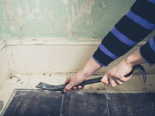 Woman prying nail with crowbar