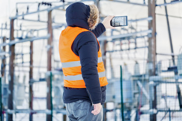 Engineer filmed with tablet PC at power plants in winter