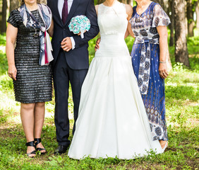 newlywed couple  with guests  in green sunny park