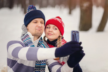 Couple in love makes a picture a selfie in winter Park on Valentine's day.