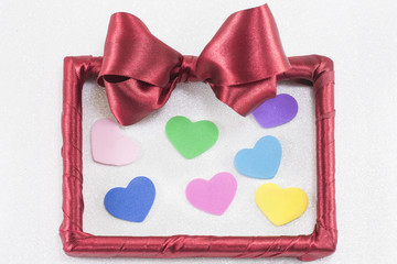 empty picture frame with red ribbon with colorful hearts