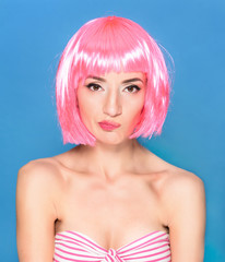 Confused young woman with pink hair on a blue background