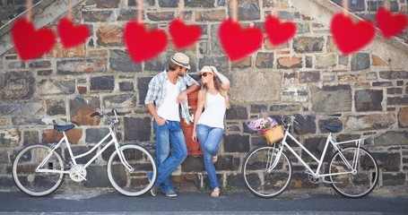 Composite image of attractive couple standing with bikes