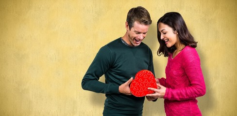 Composite image of happy young couple with heart shape gift