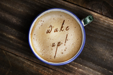 Words wake up formed from coffee foam. Cup of cappuccino coffee on wooden table.