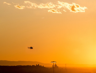 Helicopter is flying in the sunset