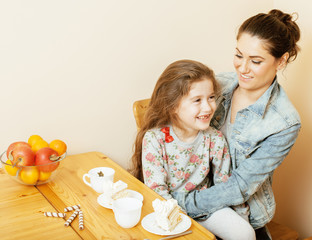 young mother with daughter on kitchen drinking tea together hugging eating celebration cake birthday