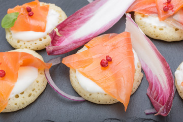 fish salmon slices on pancakes with cream, view from above on the side, close, color image. an appetizer for a party