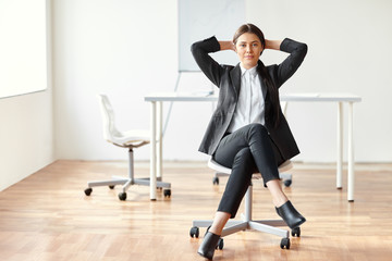 Portrait of beautiful business woman sitting on chair in the off