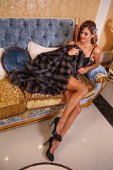 Tall blond girl showing her long legs sitting at antique style sofa and wearing lingerie bodysuit and mink fur coat