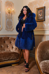 Full figure model posing sexy at the living room, wearing lingerie and deep blue fur coat
