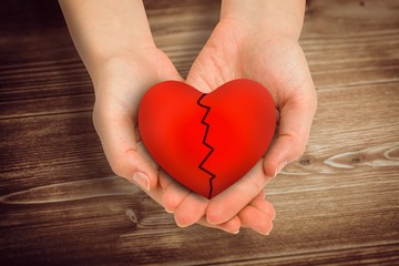 Composite image of couple holding broken heart in hands