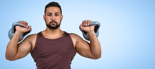 Composite image of muscular serious man lifting kettlebells