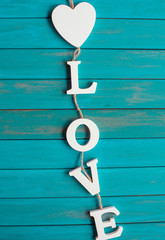Vintage white wooden letters love on a blue background. Love decoration.