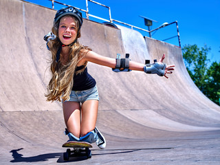 Sport girl rides his skateboard outdoor.