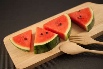 water melon slice on wood plate with fork and spoon isolated on black background