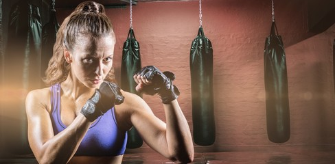 Confident female boxer with fighting gloves