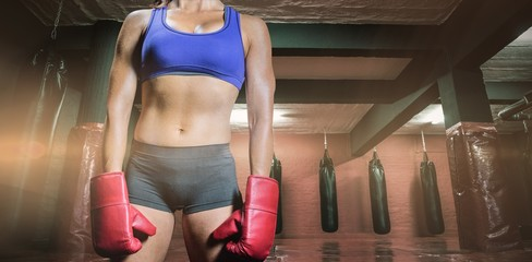 Composite image of midsection of female boxer with gloves
