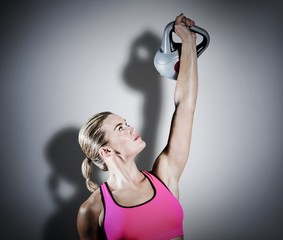 Composite image of muscular woman lifting heavy kettlebell