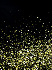 Photo of golden glitter on a black background. Golden explosion