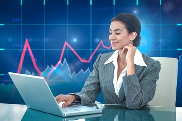 Composite image of smiling businesswoman using laptop at desk