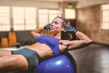 Composite image of woman exercising on ball