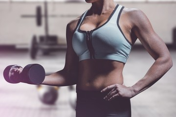 Composite image of midsection of woman lifting dumbbell
