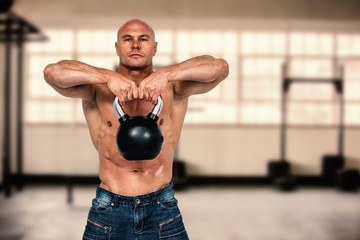 Bald man exercising with kettlebell