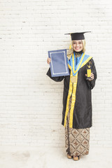 indonesian female graduate student  wearing graduation gown whil